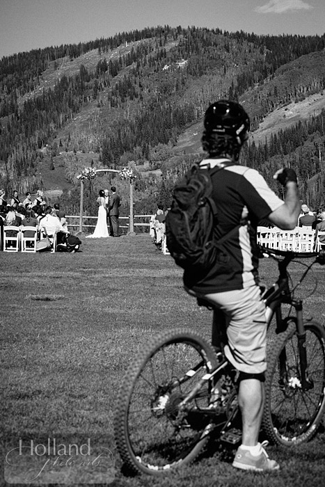 Mountain biker looks on during ceremony at L&R's Steamboat Springs wedding
