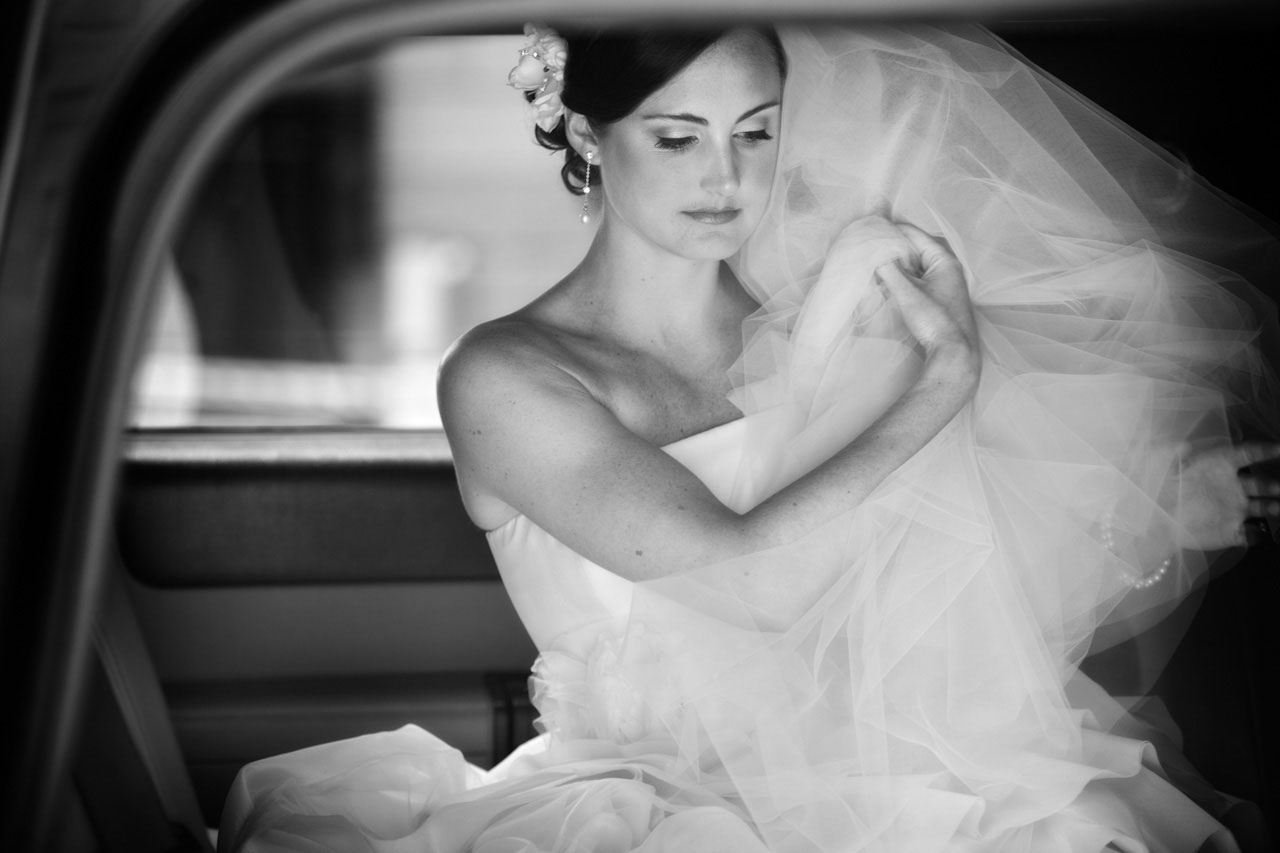 Serene bride wearing Vera Wang wedding gown adjusting her veil before getting out of limo before ceremony, wedding photography, Washington, DC