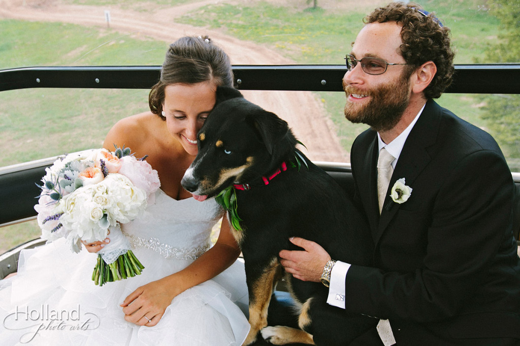 Bride and groom with dog licking bride's face on gondola ride at Vail on way to wedding deck
