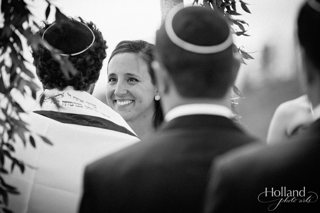 Bride smiles at groom during Jewish ceremonyt  at Vail wedding deck