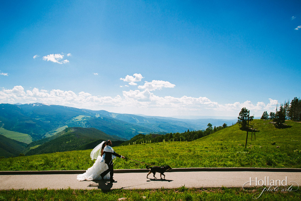Bride, groom, and dog recess with Rocky mountains in background from Vail wedding deck