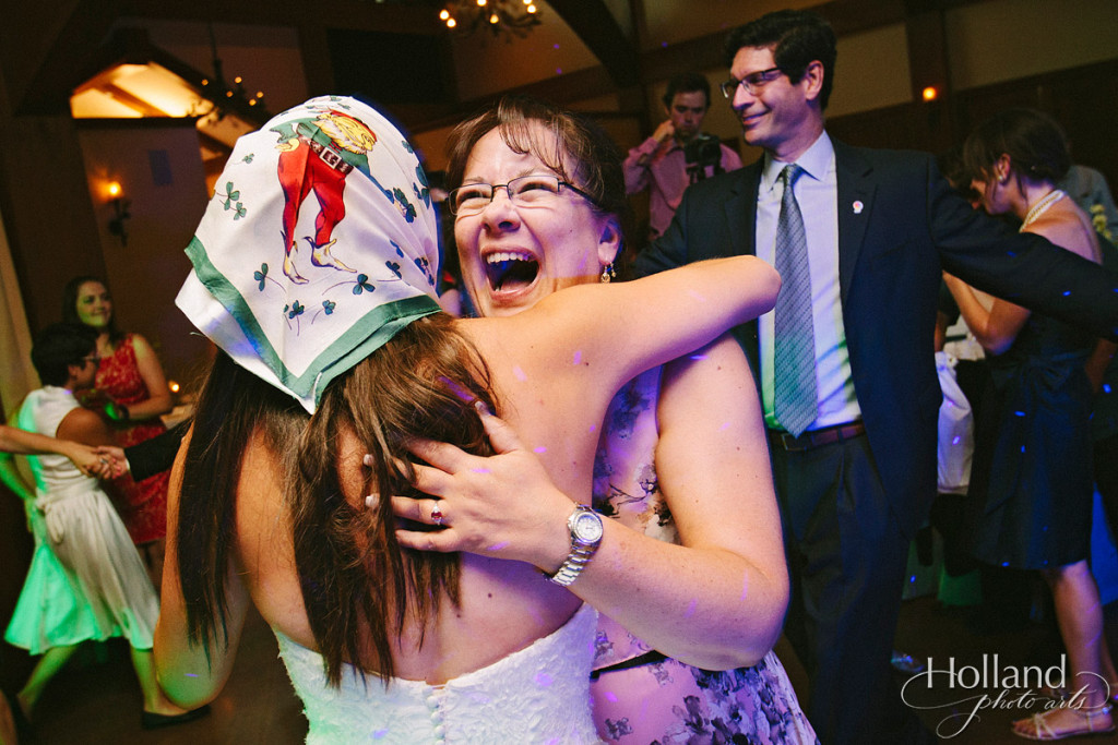 Bride hugs friend at wedding reception at Donovan Pavillion