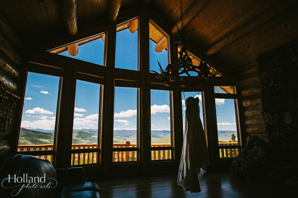 Wedding dress silhouette in rustic cabin against Rocky Mountains