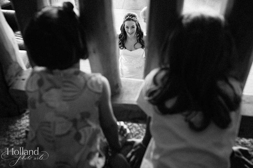 Bride looks up at flower girls as she puts on her dress