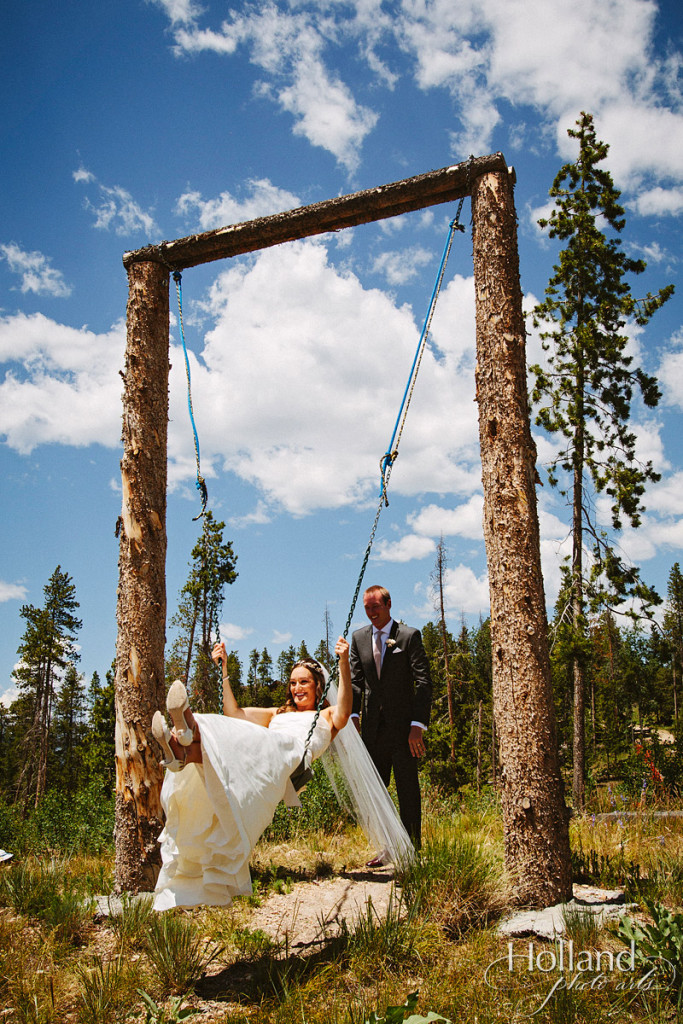 Bride swings on custom swing in middle of pine trees