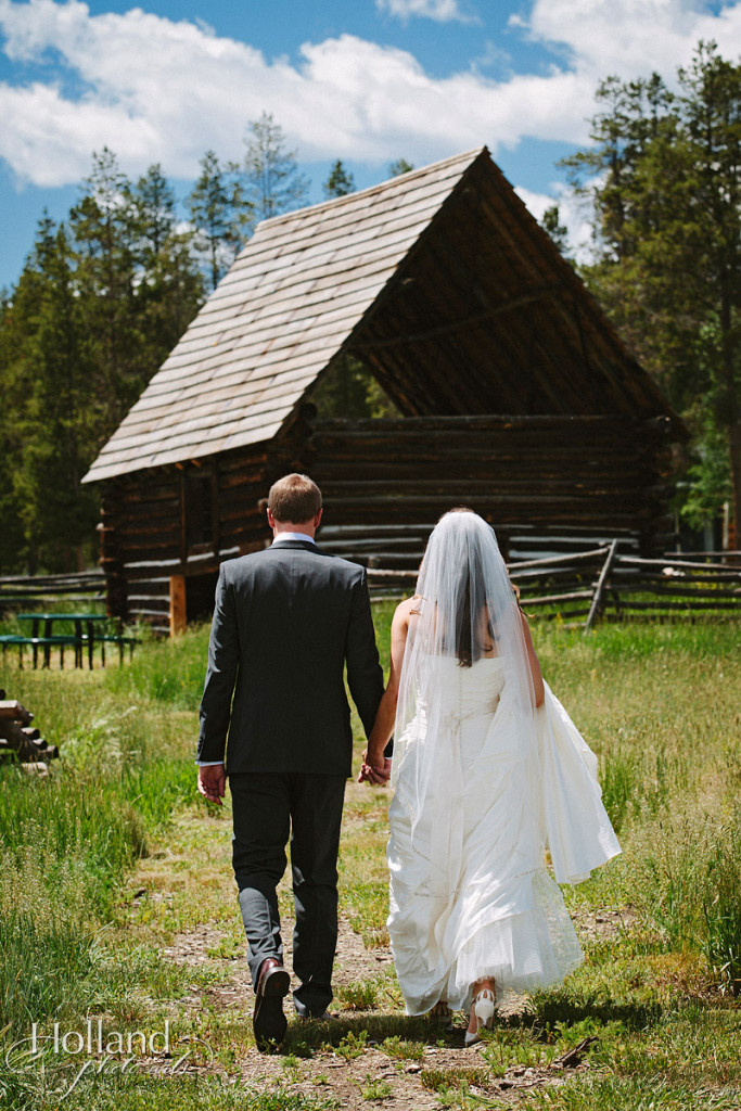 Bride and groom walk in field toward rustic barn