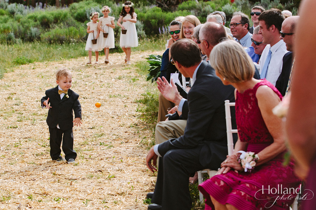 Ring bearer throws fruit near guests with flower girls in background