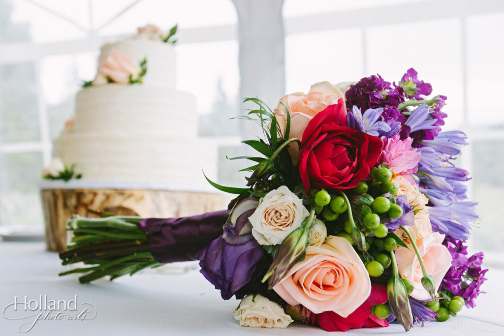 Bridal bouquet with wedding cake in background
