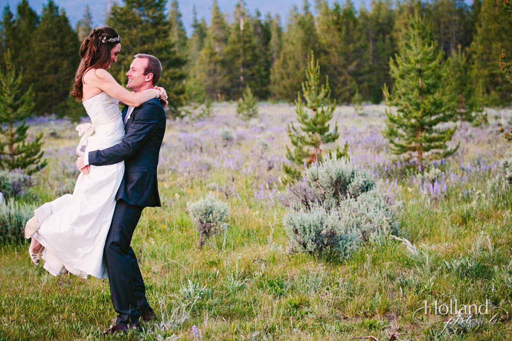 Bride and groom play at dusk with Rocky mountains in background