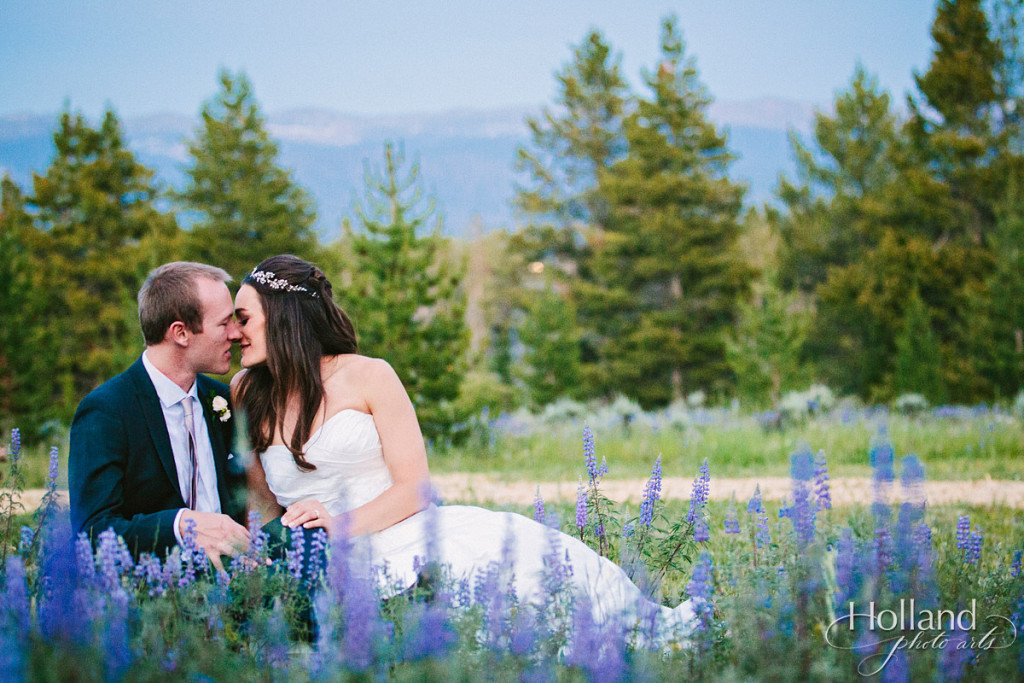 Bride and groom tender moment with Rocky mountains in background